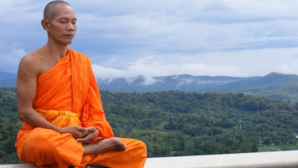 Monk sitting with mountains in back 2.jpg