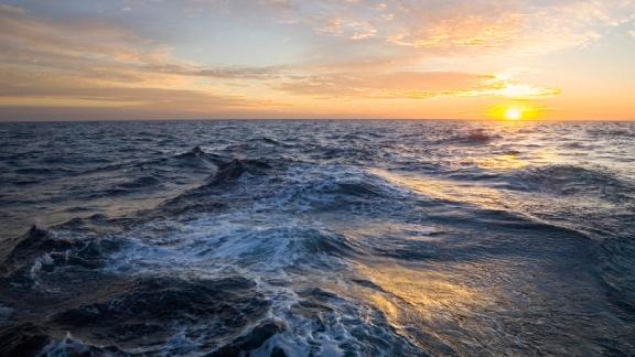 Golden sunrise clouds over ocean